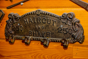 Antique metal coat hanger that says 'Haircut and Shave 25¢'